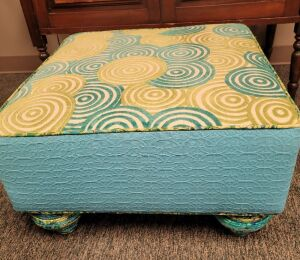 Expertly and Artistically Upholstered Ottoman from Funky Fibers. This cmodern design is 24 inches square and 15 inches tall. The legs are also craftily upholstered.